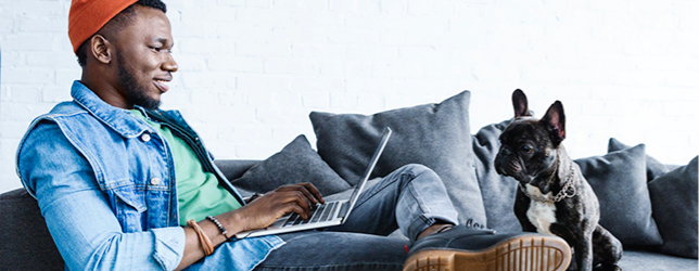 Young, hip male on couch with his laptop.