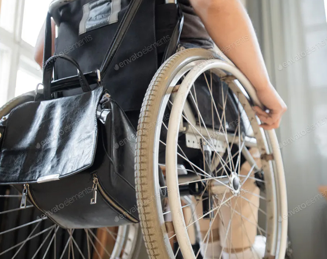 Wheelchair of young contemporary businesswoman moving towards colleague.